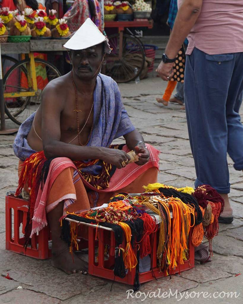 Priest selling sacred threads atop Chamundi Hills